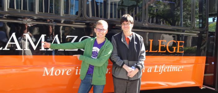 Students in front of a Kalamazoo College bus to take them to Detroit for French Day.